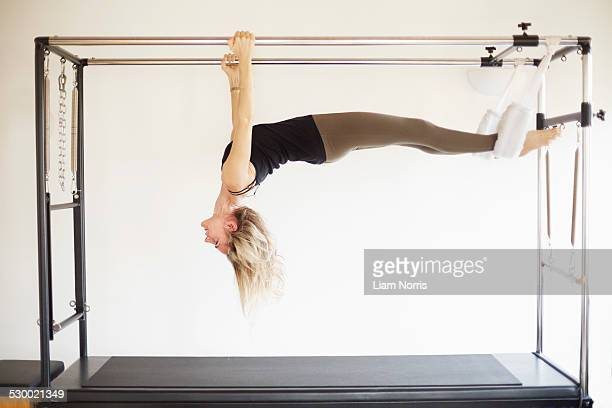 Mature woman practicing pilates on trapeze table in pilates gym