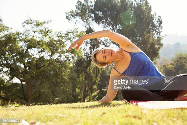 Mature woman practicing yoga in park