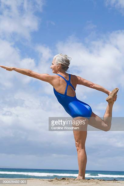 Mature woman practicing yoga on beach, side view