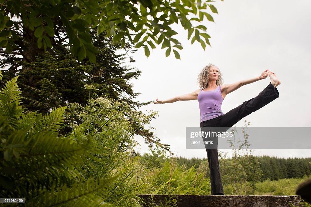 Mature woman practicing yoga pose on footbridge