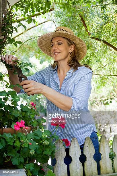 Reife Frau Stutzen Blumen im Garten, Lächeln