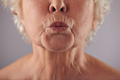 Close-up portrait of mature woman puckering lips against grey background. Senior woman grimacing. Focus on lips.