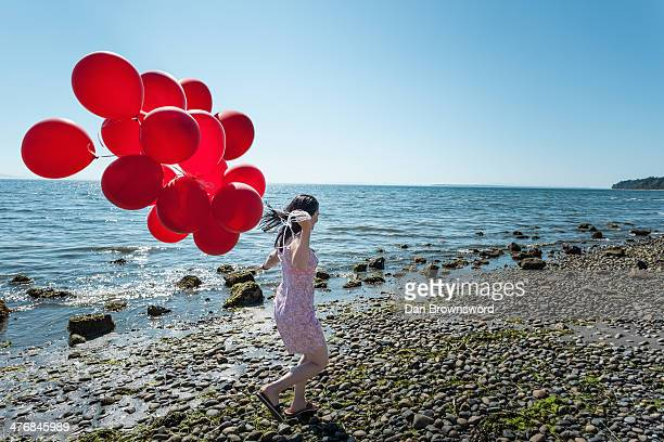 Mature woman pulling bunch of balloons
