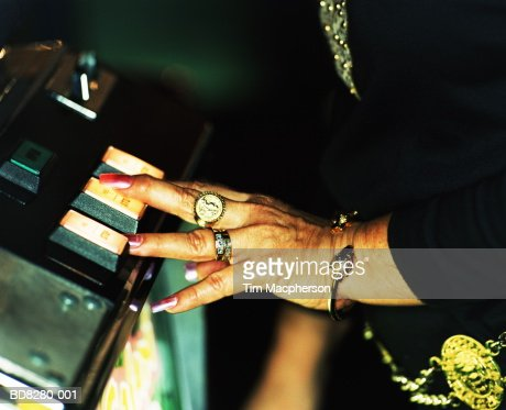 Mature woman pushing fruit machine button, close-up : Stock Photo