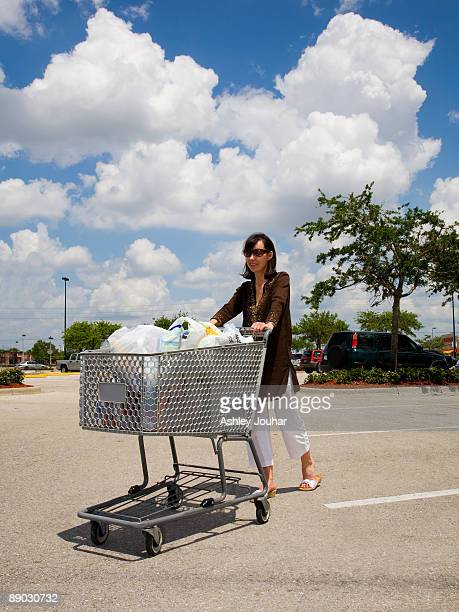 Mature woman pushing groceries in shopping cart