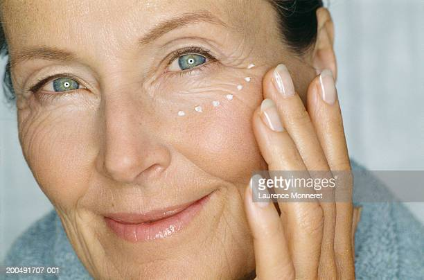 Mature woman putting cream under eyes, smiling, close-up, portrait