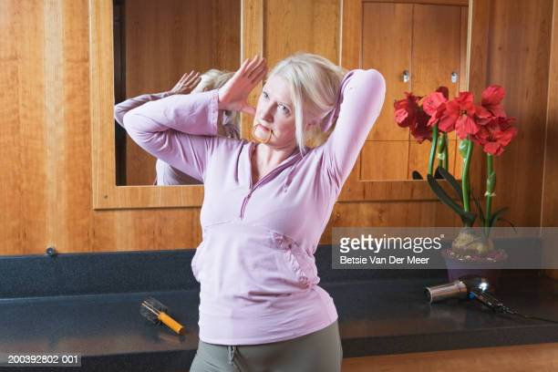 Mature woman putting hair up in gym changing room
