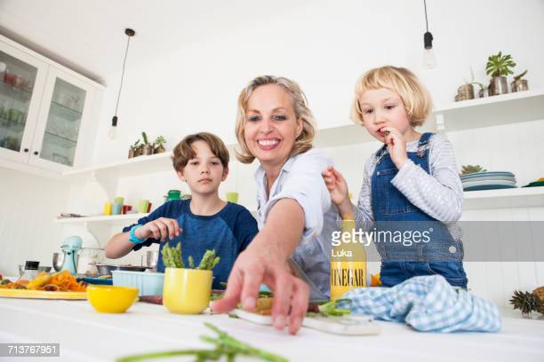 Mature woman reaching for asparagus at kitchen table with son and daughter