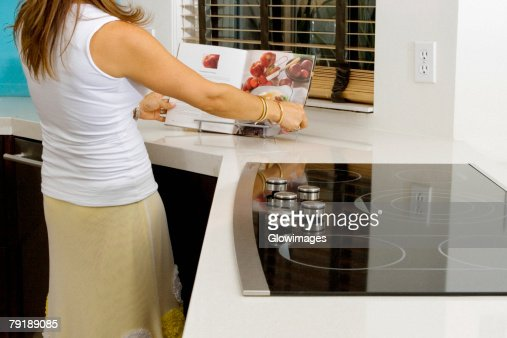 Mature woman reading a cookbook at a kitchen counter : Foto de stock