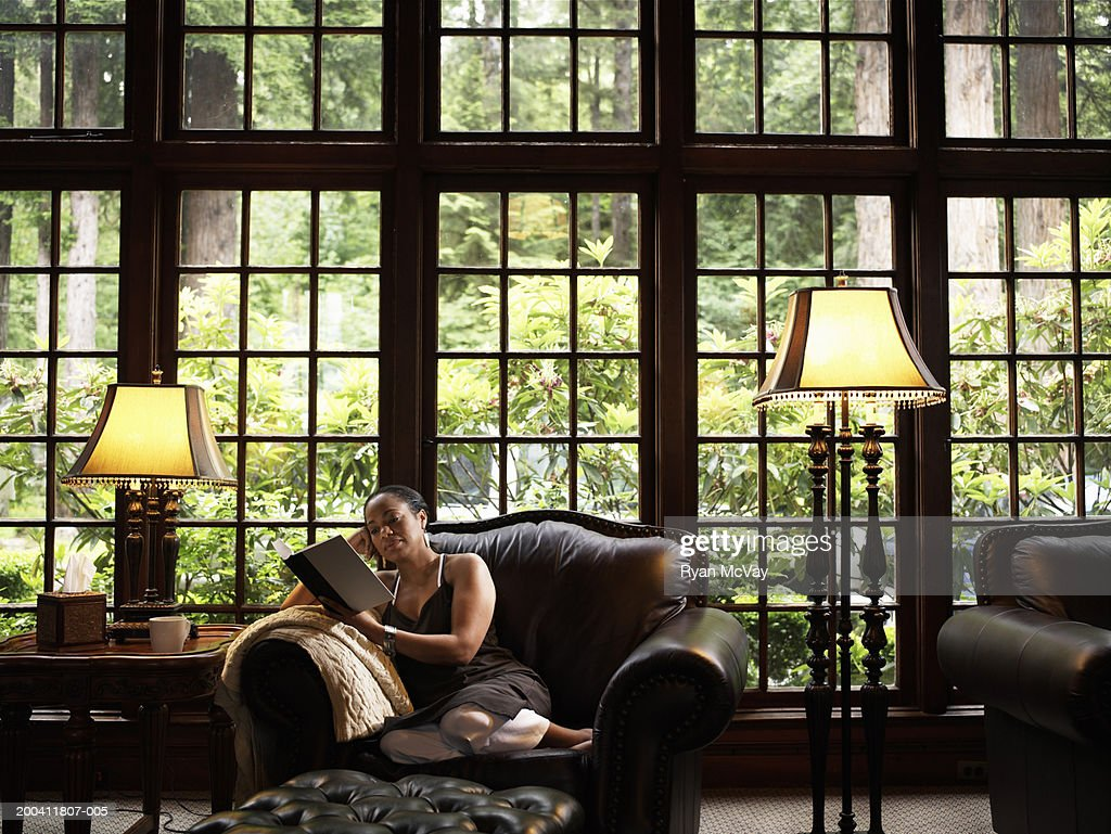 Mature woman reading book on leather armchair in lobby of lodge : Stock Photo