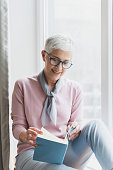 Attractive mature woman reading book in her bright modern cosy home, Enjoying free time and reading book concept