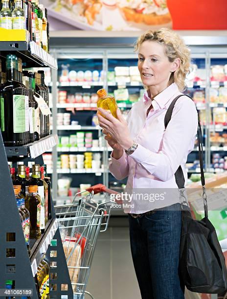 mature woman reading bottle label in supermarket