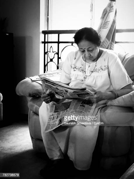 Mature Woman Reading Newspaper While Sitting On Sofa At Home