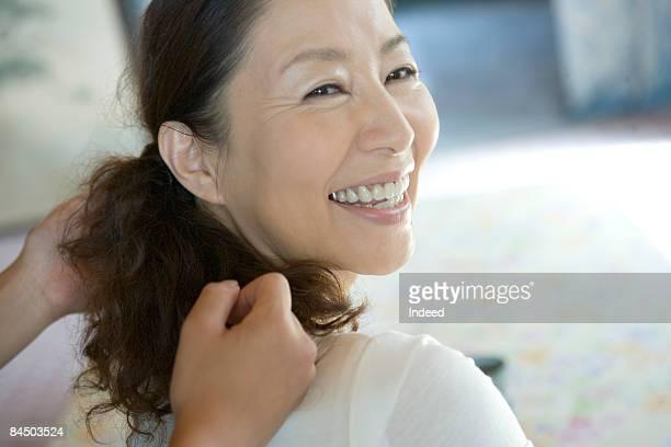 Mature woman receiving shoulder massage, smiling