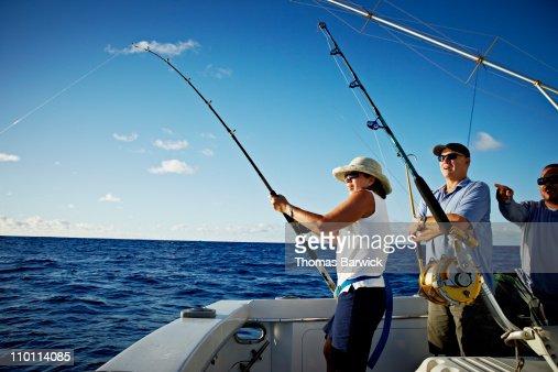 Mature woman reeling in fish : ストックフォト