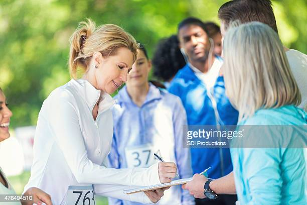 Mature woman registering to compete in marathon or 5k race