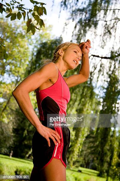 Mature woman relaxing after jogging in park