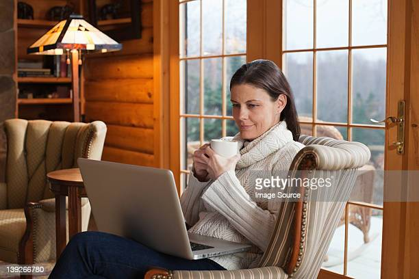Mature woman relaxing in armchair with laptop