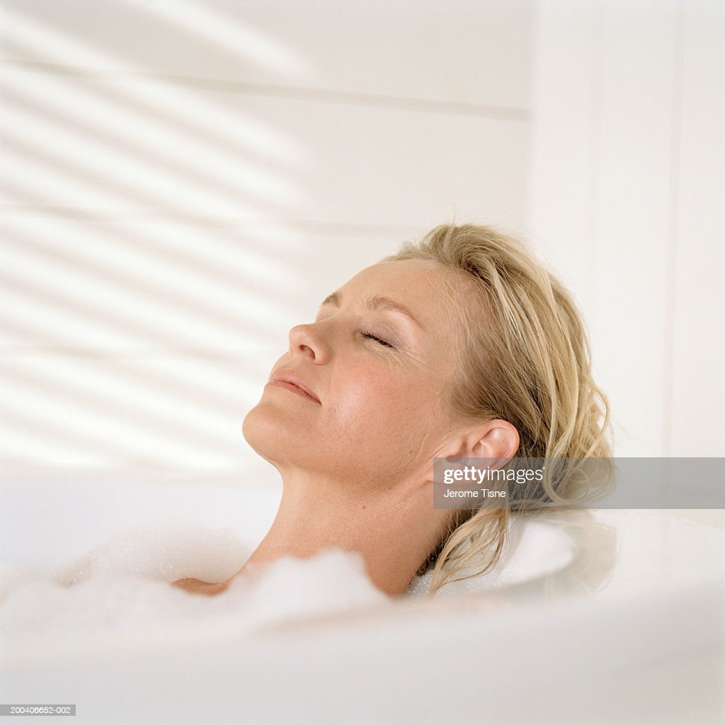 Mature woman relaxing in bubble bath, side view : Stock Photo