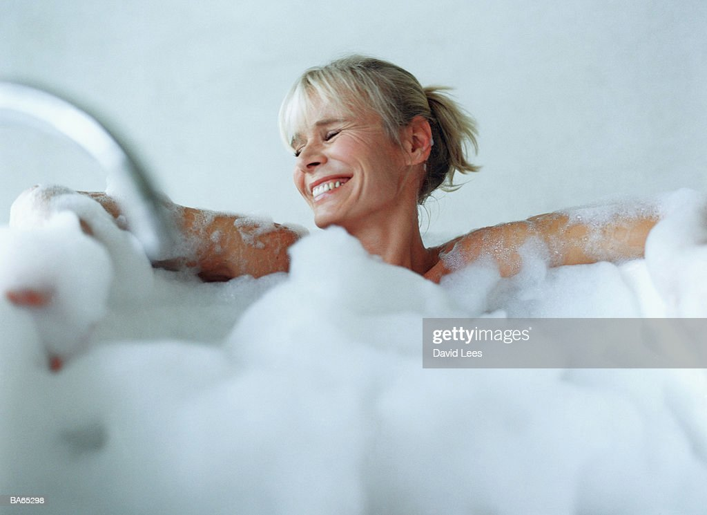 Mature woman relaxing in bubble bath, smiling : Stock Photo