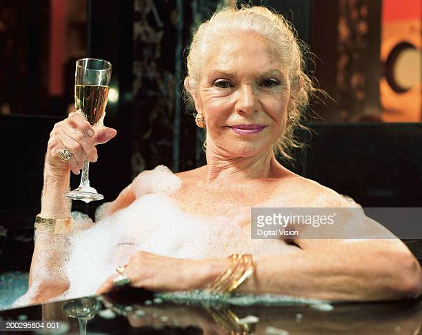 Mature woman relaxing in hot tub, holding champagne flute, portrait