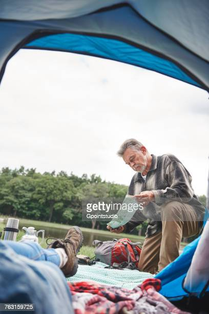 Mature woman relaxing in tent, man outside tent, looking at map