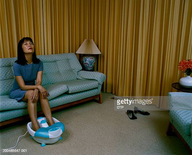 Mature woman relaxing on couch with footspa