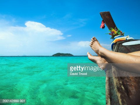 Mature woman relaxing on longtail boat, low section