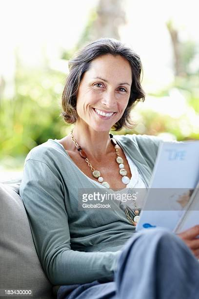 Mature woman relaxing on sofa and enjoying reading a magazine