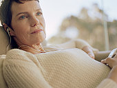 Mature woman relaxing on sofa, listening to MP3 player, close-up