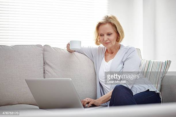 Mature woman relaxing on sofa using laptop