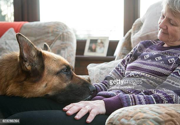 Mature woman relaxing with German Shepherd Dog