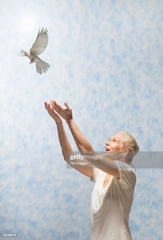 Mature woman releasing dove