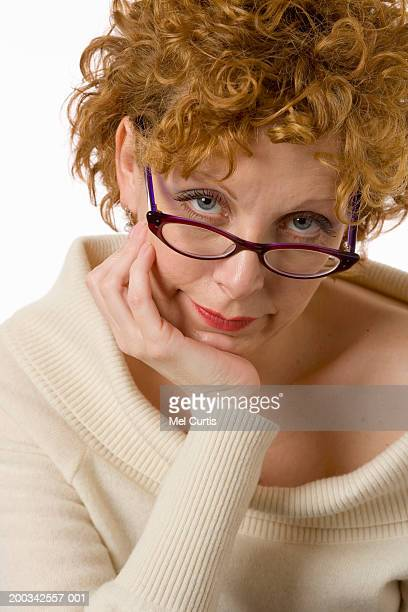 Mature woman resting chin on hand, looking over top of glasses