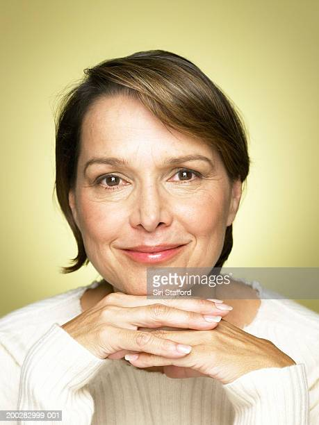 Mature woman resting chin on hands, portrait