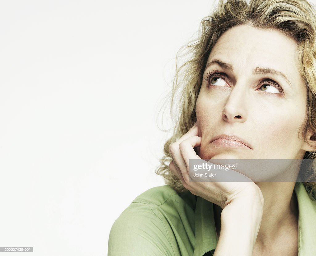 Mature woman resting head on hand, looking up, close-up : Stock Photo