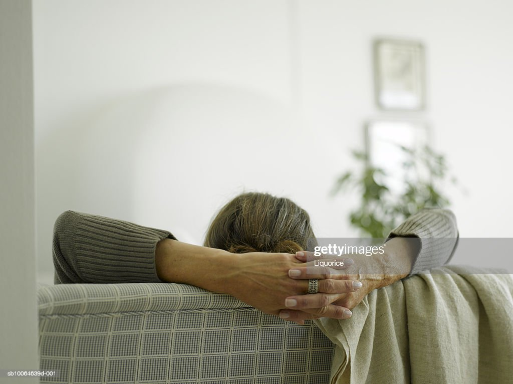 Mature woman resting on chair, hands clasped, close-up : Stock Photo