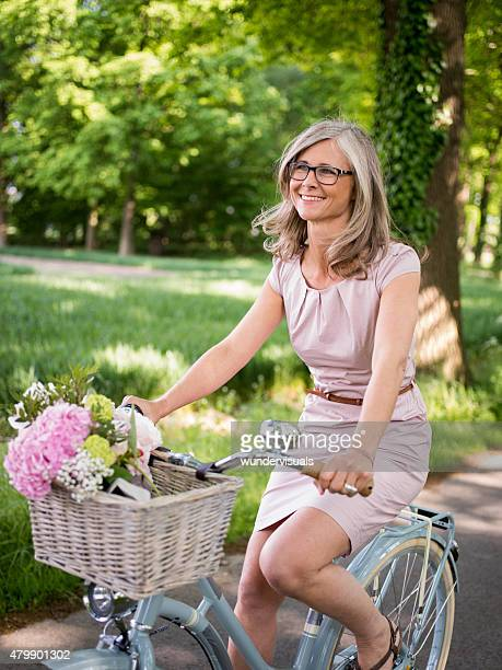 Mature woman riding a vintage bicycle in a park