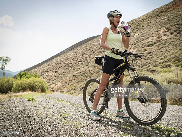 Mature woman riding bike on mountain road