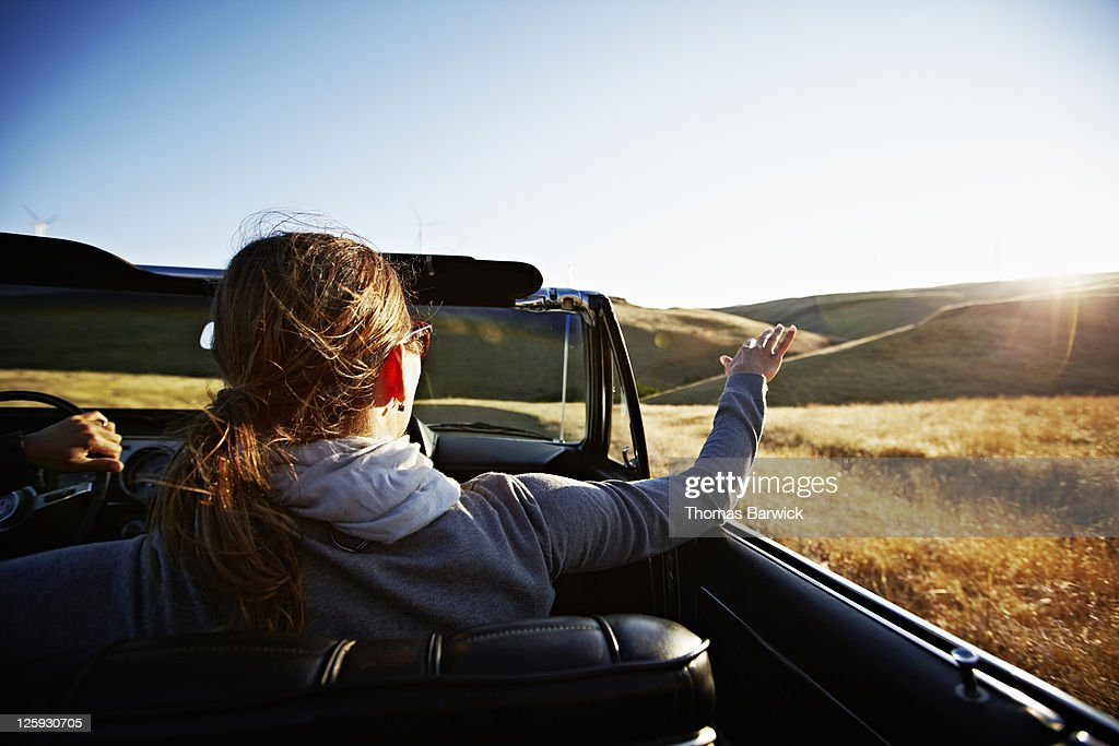 Mature woman riding in convertible at sunset : Stock Photo