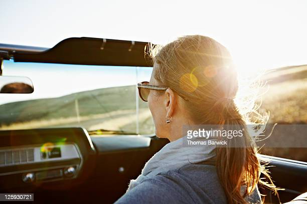 Mature woman riding in convertible at sunset