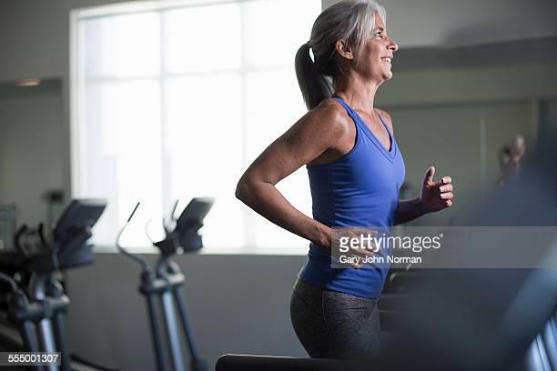 Mature woman running on gym treadmill