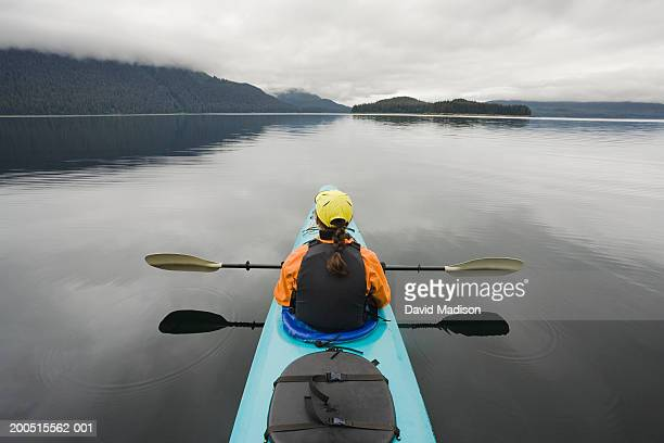 Mature woman sea kayaking, rear view