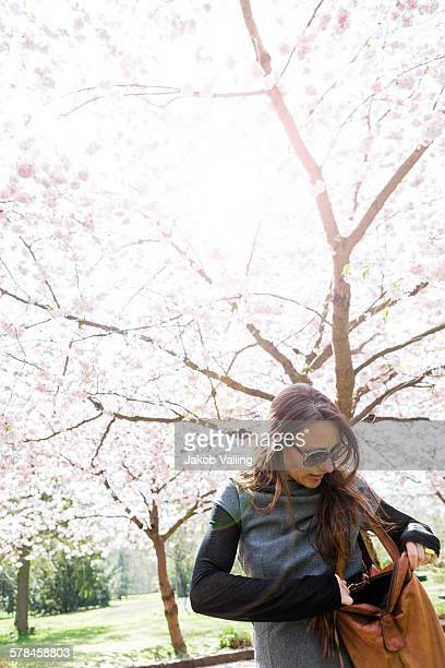 Mature woman searching through shoulder bag in front of cherry blossom