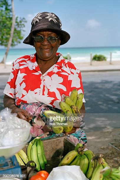 Mature woman selling bananas in street, portrait