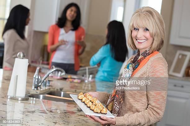 Mujer madura se sirven aperitivos con amigos en la fiesta de inicio