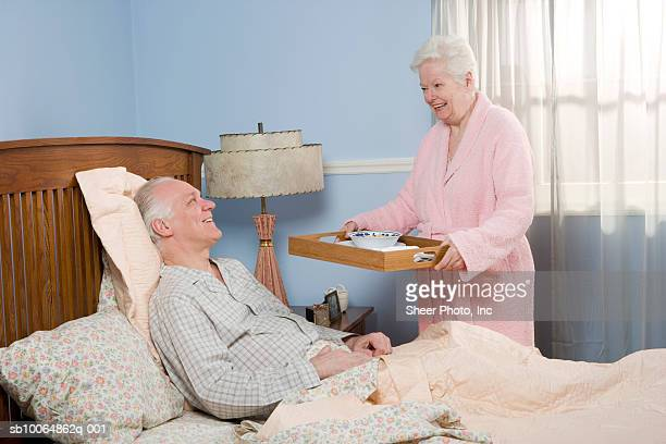 Mature woman serving senior man soup in bed