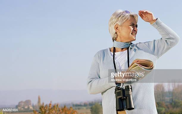 Mature woman shielding sun from her eyes, high section