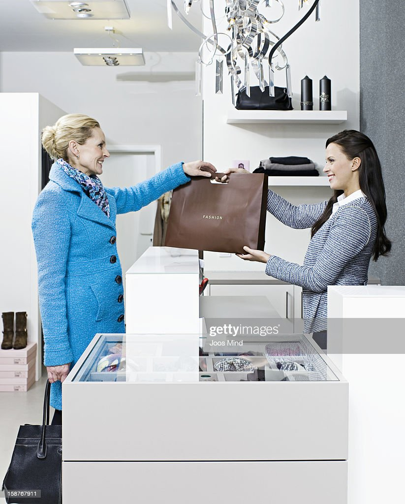 mature woman shopping in clothing store : Stock Photo