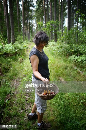 Mature Woman Showing Off A Basket Of Wild Mushrooms In A Forest ...